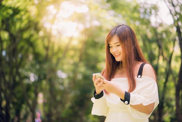 Donna asiatica carina sta leggendo un messaggio di testo piacevole sul telefono cellulare mentre si siede nel parco in una giornata di primavera calda, femmina splendida ascoltando musica nelle cuffie e ricerca di informazioni sul telefono delle cellule.