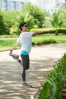 Donna asiatica che allunga nel parco