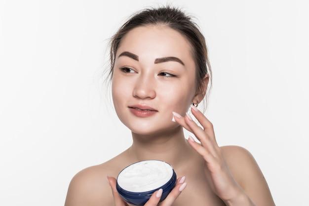 Donna asiatica che applica crema cosmetica sul fronte di cura di pelle facciale sull'isolato sulla parete bianca