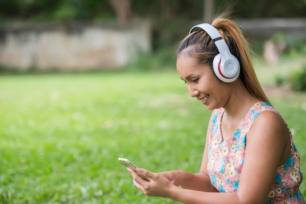 Donna asiatica che ascolta musica favorita sulle cuffie. buon momento e relax.