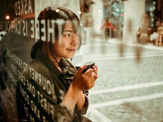 Donna asiatica che beve caffè nella caffetteria