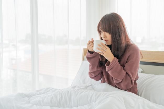 Donna asiatica che beve il caffè sul letto la mattina