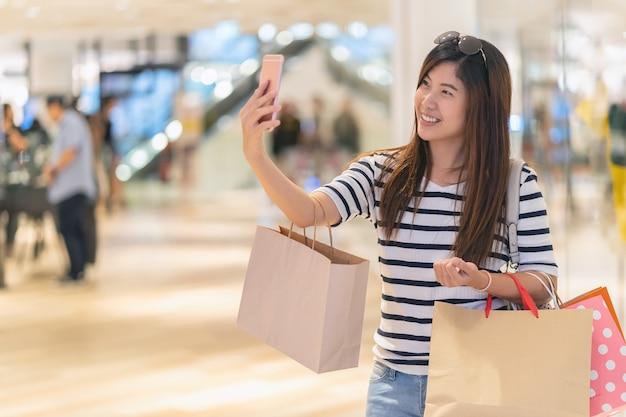 Donna asiatica che cammina e che utilizza il telefono cellulare intelligente per selfie con modello display mockup