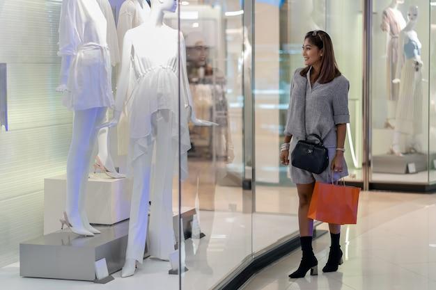 Donna asiatica che cammina e guardando attraverso il glassess nei vestiti