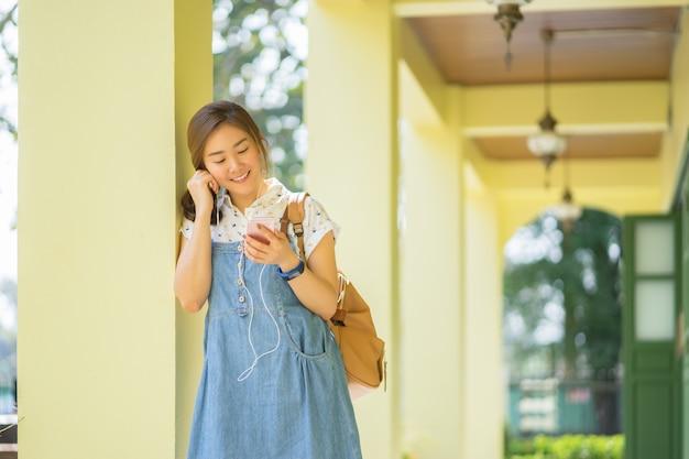 Donna asiatica che cammina e utilizza uno smart phone in strada