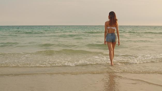 Donna asiatica che cammina sulla spiaggia di sabbia.