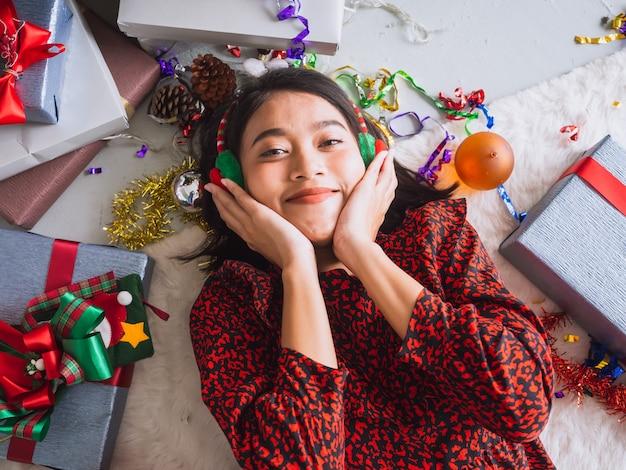 Donna asiatica che celebra nuovo anno e natale sul pavimento con il contenitore di regalo