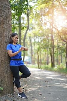 Donna asiatica che controlla il tempo dalla frequenza cardiaca astuta del controllo dell'orologio mentre pareggiando nel parco
