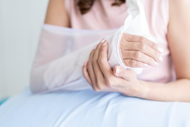 Donna asiatica che esamina il suo braccio che ha ferito dall'incidente