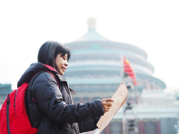 Donna asiatica che esamina la mappa nella grande sala del quadrato della gente di chongqing alla cina.