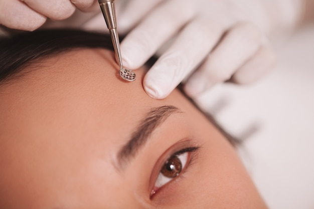 Donna asiatica che fa pulire la sua pelle da cosmetologo professionista, usando il dispositivo di rimozione del comedone