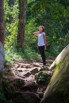 Donna asiatica che fa un'escursione nel legno.