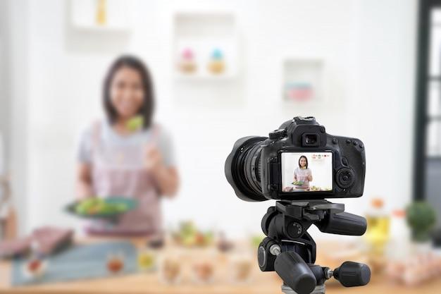 Donna asiatica che fa una macchina fotografica digitale del video di vlog per il suo blog che cucina nella stanza della cucina