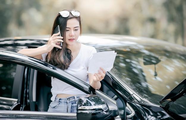 Donna asiatica che fa una pausa automobile ripartita e che per mezzo dello smartphone per assistenza.