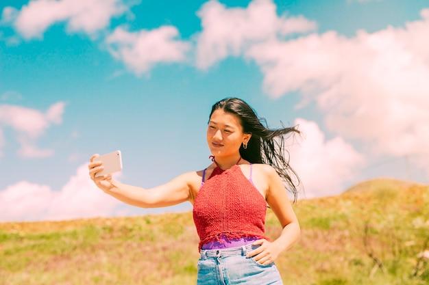 Donna asiatica che fotografa nel campo