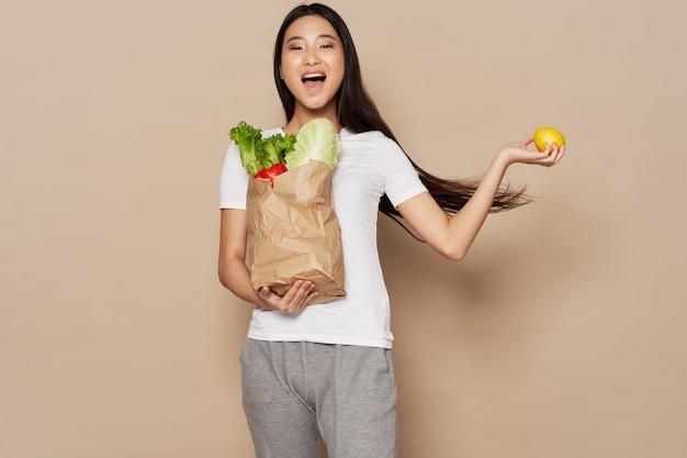 Donna asiatica che giudica un sacco di carta pieno di alimento sano