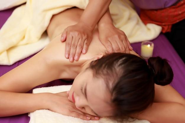 Donna asiatica che gode di un massaggio di sfregatura alla stazione termale.