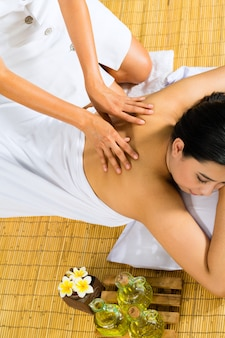 Donna asiatica che ha un massaggio nella regolazione tropicale