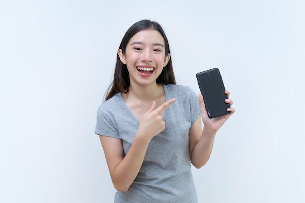 Donna asiatica che indica telefono cellulare, holding, cellulare dello schermo in bianco