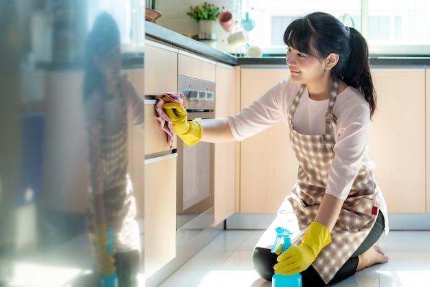 Donna asiatica che indossa guanti protettivi di gomma che puliscono gli armadietti della cucina nella sua casa durante il soggiorno a casa usando il tempo libero per la loro routine di pulizia quotidiana.