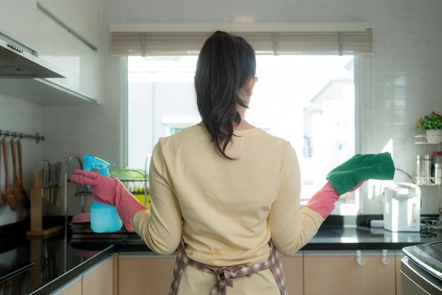 Donna asiatica che indossa guanti protettivi di gomma rosa, con straccio e detersivo per bottiglie spray.