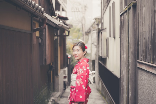 Donna asiatica che indossa il kimono giapponese tradizionale che cammina nella vecchia città di kyoto