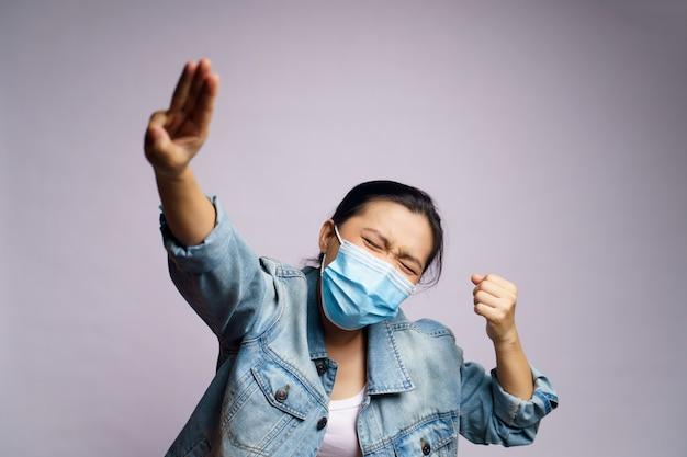 Donna asiatica che indossa la maschera protettiva che mostra tre dita isolate.