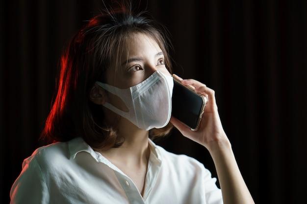 Donna asiatica che indossa maschera chirurgica e che fa una telefonata