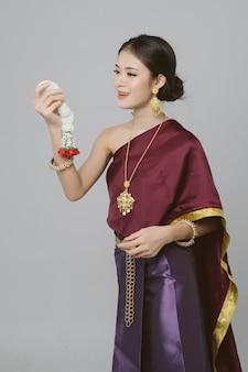 Donna asiatica che indossa un abito tradizionale tailandese su sfondo grigio