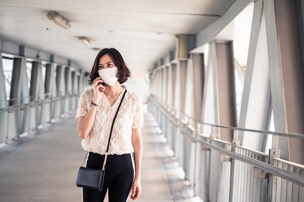 Donna asiatica che indossa una maschera per prevenire il crepuscolo pm 2.5 cattivo inquinamento dell'aria e coronavirus, covid-19 che si diffonde in asia usando una telefonata sul cellulare.