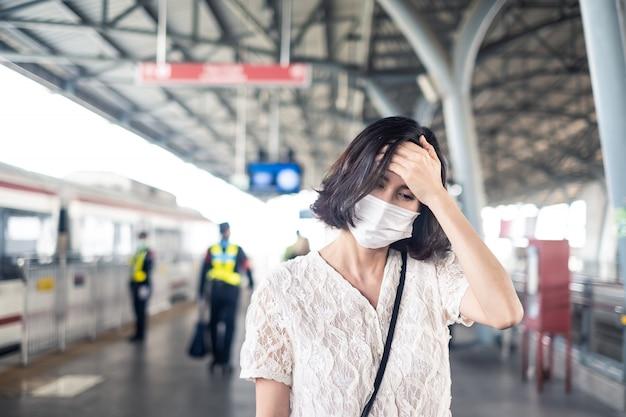 Donna asiatica che indossa una maschera per prevenire il crepuscolo pm 2.5 cattivo inquinamento dell'aria e coronavirus o covid-19 che si diffondono in asia con mal di testa sul treno a cielo.
