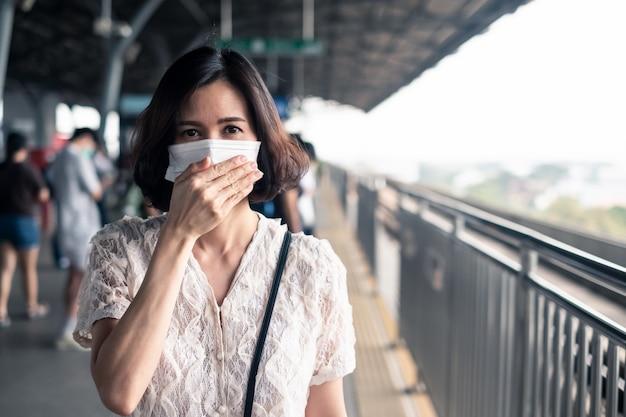 Donna asiatica che indossa una maschera per prevenire il crepuscolo pm 2.5 cattivo inquinamento dell'aria e coronavirus o covid-19 che si diffondono in asia.