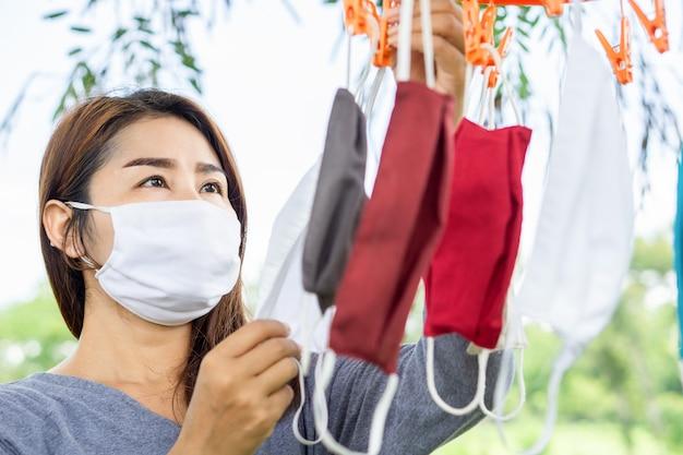 Donna asiatica che lava e che appende per asciugare la maschera di protezione del tessuto