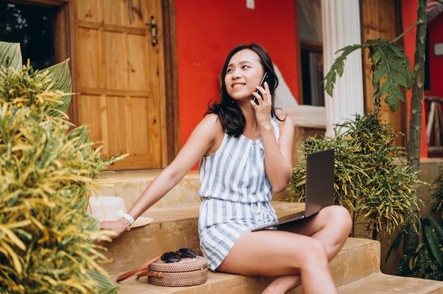 Donna asiatica che lavora al computer portatile su una vacanza e che si siede sulle scale