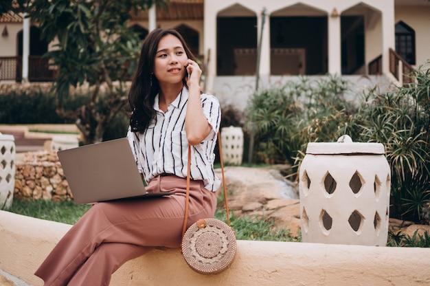 Donna asiatica che lavora al computer portatile su una vacanza
