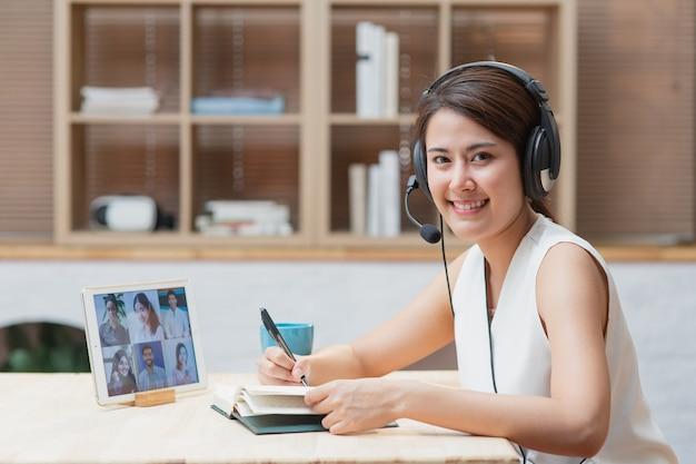 Donna asiatica che lavora da casa con riunione in linea di videoconferenza con il team di colleghi di diversità utilizzando il computer portatile