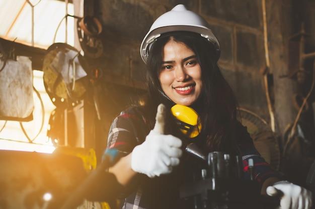 Donna asiatica che lavora in fabbrica, industria che utilizza macchina con felice.