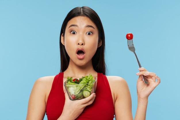 Donna asiatica che mangia insalata