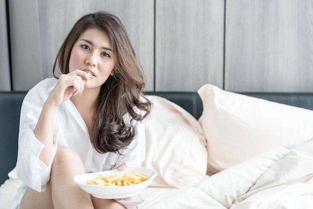 Donna asiatica che mangia le patate fritte