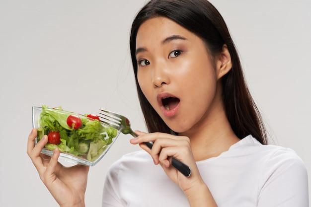 Donna asiatica che mangia un'insalata sana, concetto di dieta