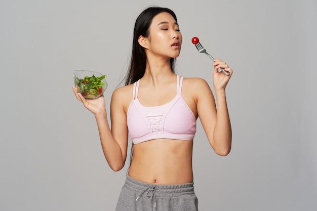 Donna asiatica che mangia un'insalata