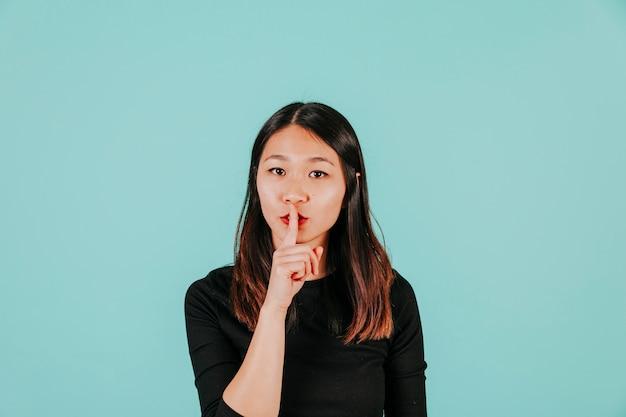 Donna asiatica che mostra gesto di silenzio