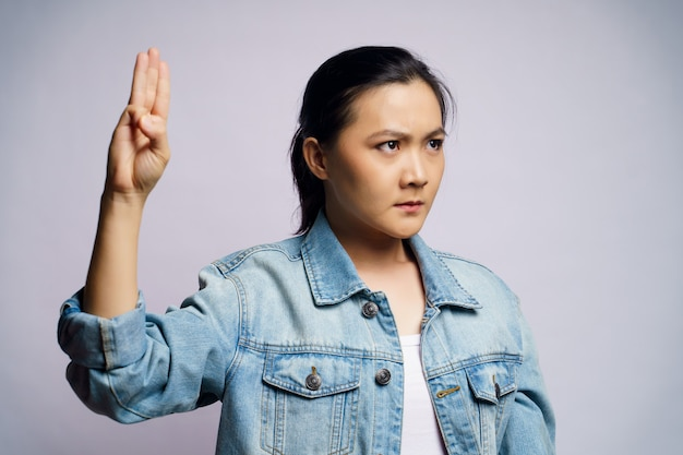 Donna asiatica che mostra tre dita isolate.