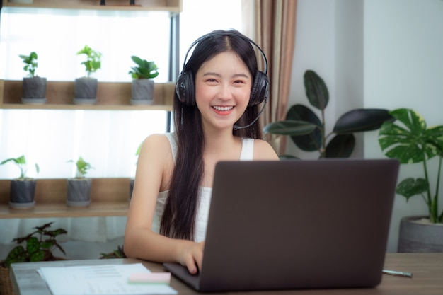 Donna asiatica che parla con altri membri dell'incontro dal desktop del computer e dalla conferenza di vidio