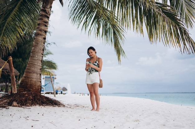 Donna asiatica che parla sul telefono alla spiaggia