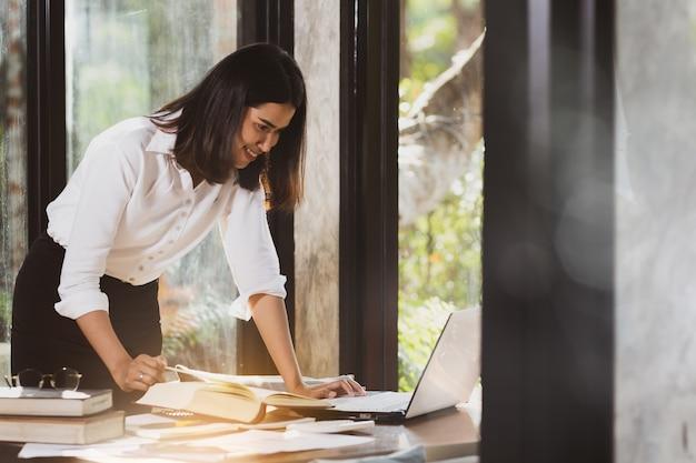 Donna asiatica che per mezzo del computer portatile che lavora con felice.