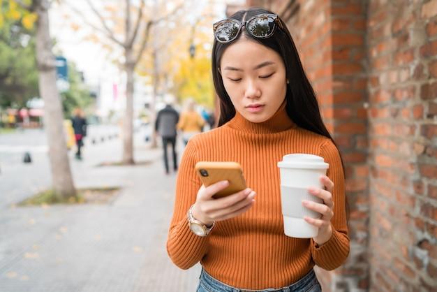 Donna asiatica che per mezzo del suo telefono cellulare.