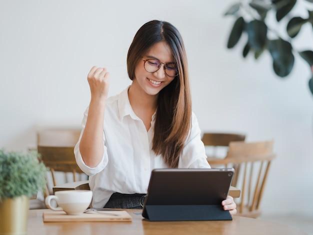 Donna asiatica che per mezzo della compressa con gli affari di successo