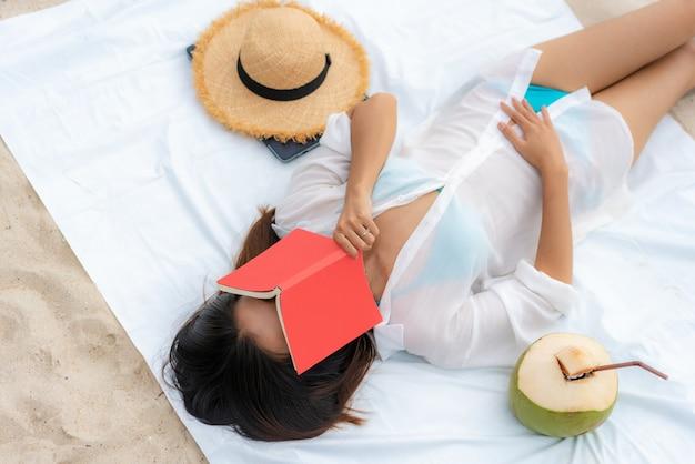 Donna asiatica che pone sulla spiaggia con un libro sul suo fronte