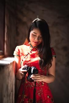Donna asiatica che porta vestito rosso che osserva sulla macchina fotografica a controllare foto che lei ha contenuto in lombate